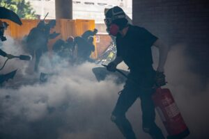 University students and protesters react after police fire tear gas to the campus of the Hong Kong Polytechnic University during a protest on November 11, 2019. – A Hong Kong police officer shot at masked protesters — hitting at least one in the torso — during clashes broadcast live on Facebook, as the city's rush hour was interrupted by protests. (Photo by Philip FONG / AFP)