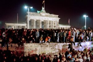 "(FILES) In this file photo taken on November 11, 1989 Thousands of young East Berliners crowd atop the Berlin Wall, near the Brandenburg Gate (background). – The fall of the Berlin Wall in 1989, when thousands of Germans joyfully danced atop its graffiti-covered remains, to some heralded the ""end of history"" in a globalised world. Thirty years later, the return of hard frontiers made of bricks, concrete and razor wire symbolises stark new political realities that are a far cry from the West's heady optimism in the era when the Soviet bloc imploded. (Photo by GERARD MALIE / AFP)"