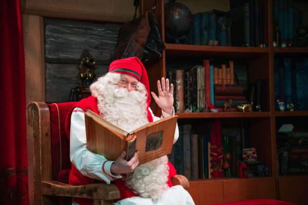 Santa Claus poses at his office near Rovaniemi, Finnish Lapland, on December 2, 2019. – Rovaniemi's Santa Claus Village amusement park is a snow-covered wonderland of reindeer rides, ice castles, souvenir shops, snowmobiles and igloo hotels where Christmas holds sway 365 days a year. But Lapland is also the homeland of the indigenous reindeer-herding Sami people, who protest that some in the tourist industry spread offensive stereotypes about Sami people and seek to profit from their ancient culture. (Photo by Jonathan NACKSTRAND / AFP)
