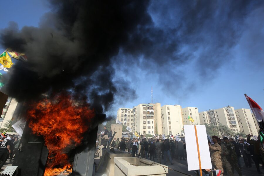 "Iraqi protesters set ablaze a sentry box in front of the US embassy building in the capital Baghdad to protest against the weekend's air strikes by US planes on several bases belonging to the Hezbollah brigades near Al-Qaim, an Iraqi district bordering Syria, on December 31, 2019. – Several thousand Iraqi protesters attacked the US embassy in Baghdad on today, breaching its outer wall and chanting ""Death to America!"" in anger over weekend air strikes that killed pro-Iran fighters. (Photo by Ahmad AL-RUBAYE / AFP)"
