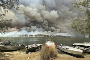 Boats are pulled ashore as smoke and wildfires rage behind Lake Conjola, Australia, Thursday, Jan. 2, 2020. Thousands of tourists fled Australia's wildfire-ravaged eastern coast Thursday ahead of worsening conditions as the military started to evacuate people trapped on the shore further south. (Robert Oerlemans via AP)