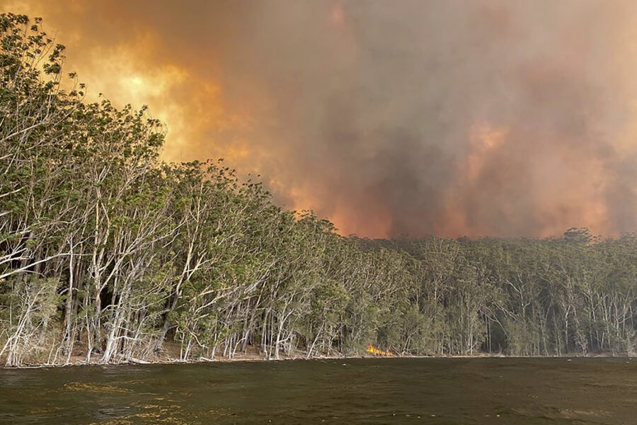 Smoke and wildfire rage behind Lake Conjola, Australia, Thursday, Jan. 2, 2020. Thousands of tourists fled Australia's wildfire-ravaged eastern coast Thursday ahead of worsening conditions as the military started to evacuate people trapped on the shore further south. (Robert Oerlemans via AP)