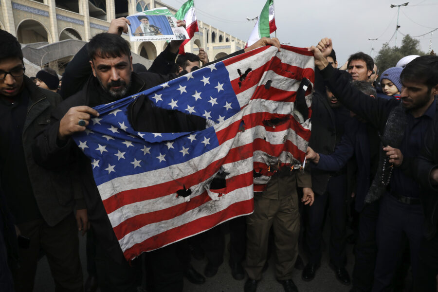 "Protesters burn a U.S. flag during a demonstration over the U.S. airstrike in Iraq that killed Iranian Revolutionary Guard Gen. Qassem Soleimani, in Tehran, Iran, Jan. 3, 2020. Iran has vowed ""harsh retaliation"" for the U.S. airstrike near Baghdad's airport that killed Tehran's top general and the architect of its interventions across the Middle East, as tensions soared in the wake of the targeted killing. (AP Photo/Vahid Salemi)"