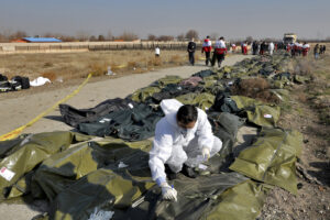 A forensic investigator works at the scene of a Ukrainian plane crash as bodies of the victims are collected, in Shahedshahr, southwest of the capital Tehran, Iran, Wednesday, Jan. 8, 2020. A Ukrainian airplane carrying 176 people crashed on Wednesday shortly after takeoff from Tehran's main airport, killing all onboard. (AP Photo/Ebrahim Noroozi)
