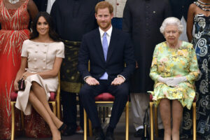 """FILE – In this Tuesday, June 26, 2018 file photo Britain's Queen Elizabeth, Prince Harry and Meghan, Duchess of Sussex pose for a group photo at the Queen's Young Leaders Awards Ceremony at Buckingham Palace in London. In a stunning declaration, Britain's Prince Harry and his wife, Meghan, said they are planning """"to step back"""" as senior members of the royal family and """"work to become financially independent."""" A statement issued by the couple Wednesday, Jan. 8, 2020 also said they intend to """"balance"""" their time between the U.K. and North America. (John Stillwell/Pool Photo via AP, File)"""