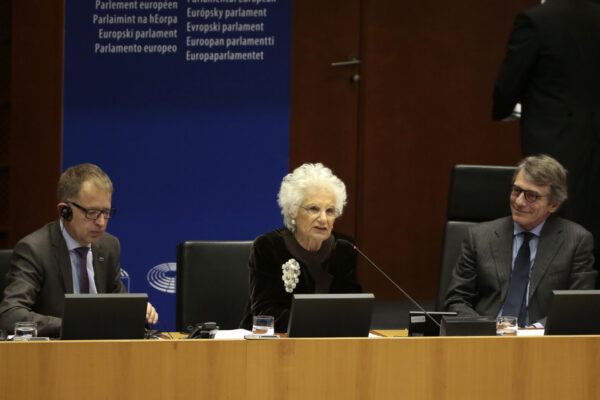 Liliana Segre, senator for life, Senato della Repubblica and survivor of Auschwitz, center, speaks during a ceremony to remember victims of the Holocaust at the European Parliament in Brussels, Wednesday, Jan. 29, 2020. (AP Photo/Virginia Mayo)