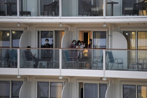 "Passengers from the cruise ship ""World Dream"" docked at Kai Tak cruise terminal, wave to family members on shore in Hong Kong, Saturday, Feb. 8, 2020. The cruise ship ""World Dream"" with approximately 1,800 passengers remained quarantined in Hong Kong's Victoria Harbour on Saturday. Several passengers from mainland China on a previous World Dream cruise were found to have the new coronavirus on returning home. (AP Photo/Kin Cheung)"