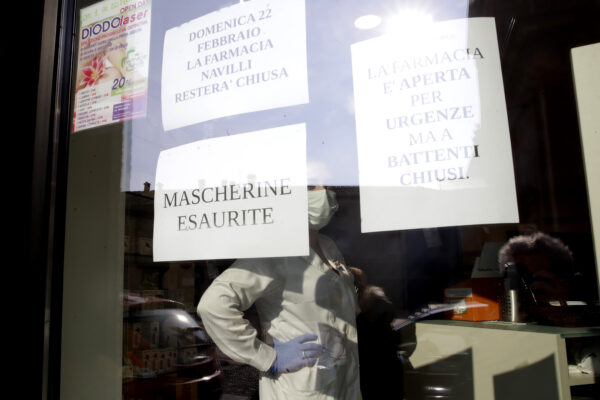 """A note reading in Italian """" Masks sold out """" hangs on the window of a pharmacy in Codogno, near Lodi, Northern Italy, Saturday, Feb. 22, 2020. A dozen towns in northern Italy are on effective lockdown after the new virus linked to China claimed a first fatality in Italy and sickened an increasing number of people. The secondary contagions have prompted local authorities in towns of Lombardy and Veneto to order schools, businesses, and restaurants closed, and to cancel sporting events and Masses. (AP Photo/Luca Bruno)"""