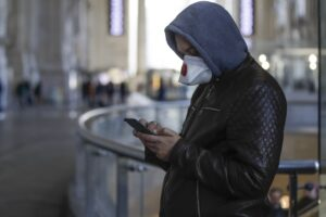 A man wearing a sanitary mask holds a smartphone at the Centrale main railway station in Milan, Italy, Monday, Feb. 24, 2020. Italy has been scrambling to check the spread of Europe's first major outbreak of the new viral disease amid rapidly rising numbers of infections and a third death, calling off the popular Venice Carnival, scrapping major league soccer matches in the stricken area and shuttering theaters, including Milan's legendary La Scala. (AP Photo/Luca Bruno)