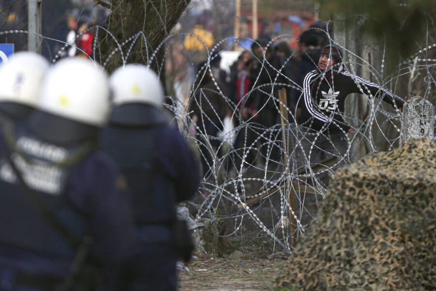 A migrant throws a stone at Greek police and army personnel during clashes near the Kastanies border gate at the Greek-Turkish border, Sunday, March 1, 2020. Migrants and refugees were trying to enter Greece by land and by sea Sunday despite Greece making clear it would not allow anyone in, after Turkey officially declared its western borders open to those hoping to head into the European Union. (AP Photo/Giannis Papanikos)