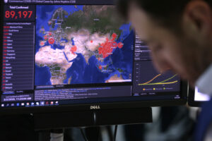 A worker at the Emergency Response Coordination Center in Brussels views a screen with graphics regarding COVID-19, Monday, March 2, 2020. European Commission President Ursula von der Leyen on Monday said the coronavirus risk level has risen from moderate to high for people living in the 27-country bloc. (AP Photo/Virginia Mayo)