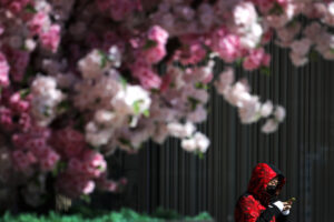 A masked woman browses her smartphone as she walks by the Wangfujing shopping district in Beijing, Tuesday, March 10, 2020. For most people, the new coronavirus causes only mild or moderate symptoms, such as fever and cough. For some, especially older adults and people with existing health problems, it can cause more severe illness, including pneumonia. (AP Photo/Andy Wong)