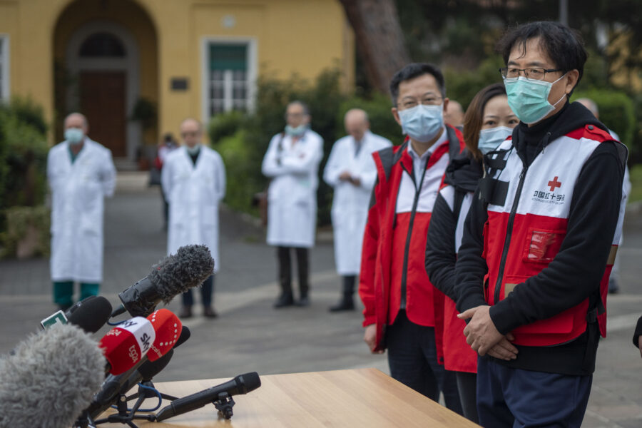 Sun Shuopeng, Vice President of China's Red Cross, right, flanked by respiratory diseases expert from the Sichuan University, Zongan Liang, third from right, speaks to journalists outside the Spallanzani Hospital for Infectious Diseases in Rome, Saturday, March 14, 2020. For most people, the new coronavirus causes only mild or moderate symptoms. For some, it can cause more severe illness, especially in older adults and people with existing health problems. In the background doctors from the Spallanzani Hospital. (AP Photo/Domenico Stinellis)