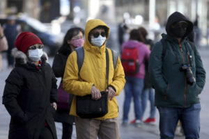 People wear protective masks downtown in Vienna, Austria, Sunday, March 15, 2020. The austrian government restricts freedom of movement. Bars and restaurants are also no longer allowed to open from Tuesday. Only for most people, the new coronavirus causes only mild or moderate symptoms, such as fever and cough. For some, especially older adults and people with existing health problems, it can cause more severe illness, including pneumonia. (AP Photo/Ronald Zak)
