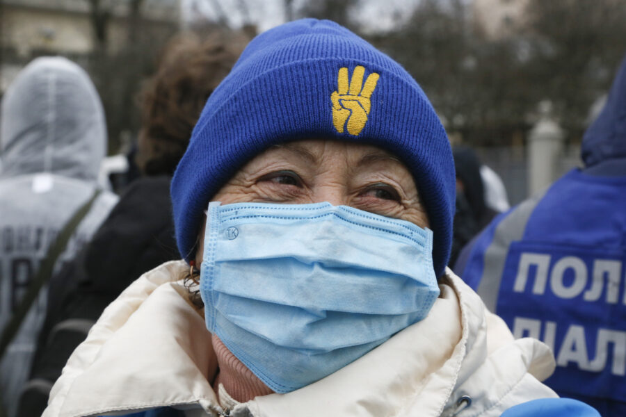 An elderly woman in a face mask smiles as she attends a rally in front of the parliament building in Kyiv, Ukraine, Tuesday, March 17, 2020. Protesters demanded lawmakers to stop working amid nation-wide quarantine in order to prevent hastily adopting unpopular laws. In an additional set of measures preventing the spread of the new coronarivus, Ukrainian authorities ruled to close public places except food markets, pharmacies and gas stations starting from Tuesday in Kyiv and other regions, and restrict the use of public transport from Kyiv to other Ukrainian cities.  For most people, the new coronavirus causes only mild or moderate symptoms. For some it can cause more severe illness, especially in older adults and people with existing health problems. (AP Photo/Efrem Lukatsky)
