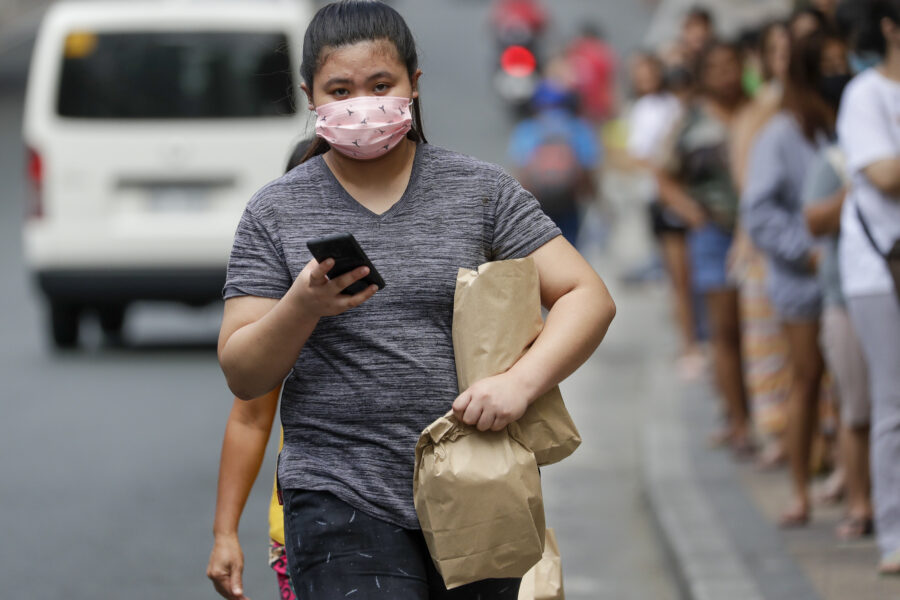 A woman wears a protective masks outside a supermarket as a precautionary measure against the spread of the coronavirus in Metro Manila, Philippines Tuesday, March 17, 2020. For most people, the new coronavirus causes only mild or moderate symptoms. For some, it can cause more severe illness, especially in older adults and people with existing health problems. (AP Photo/Aaron Favila)