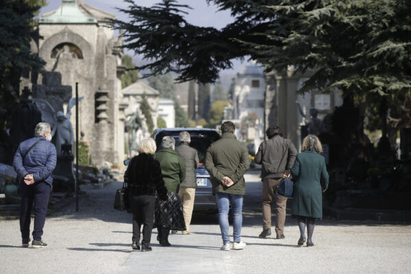 Relatives walk behind a hearse carrying a coffin inside the Monumentale cemetery, in Bergamo, Italy, Tuesday, March 17, 2020. Bergamo is one of the cities most hit by the new coronavirus outbreak in northern Italy. For most people, the new coronavirus causes only mild or moderate symptoms. For some it can cause more severe illness, especially in older adults and people with existing health problems. (AP Photo/Luca Bruno)