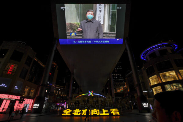People walk by a giant TV screen broadcasting news of Chinese President Xi Jinping talking to medical workers at the Huoshenshan Hospital in Wuhan in central China's Hubei Province, at a quiet shopping mall in Beijing, Tuesday, March 10, 2020. Xi visited the center of the global virus outbreak Tuesday. For most people, the new coronavirus causes only mild or moderate symptoms, such as fever and cough. For some, especially older adults and people with existing health problems, it can cause more severe illness, including pneumonia. (AP Photo/Andy Wong)