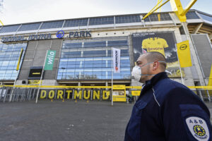 Agente di sicurezza davanti allo stadio Iduna Park di Dortmund in corso di conversione (AP Photo/Martin Meissner)