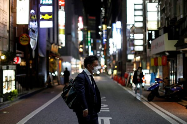A man wearing a protective face mask, following an outbreak of the coronavirus disease (COVID-19), walks at Ginza shopping and amusement district in Tokyo, Japan April 2, 2020.    REUTERS/Issei Kato