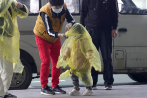 A woman wearing a face mask to protect against the spread of coronavirus puts a poncho on a child at Wuhan Tianhe International Airport in Wuhan in central China's Hubei Province, Wednesday, April 8, 2020. Within hours of China lifting an 11-week lockdown on the central city of Wuhan early Wednesday, tens of thousands people had left the city by train and plane alone, according to local media reports. (AP Photo/Ng Han Guan)