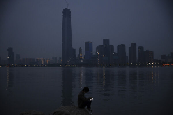 FILE – In this April 5, 2020, file photo, a man checks his mobile phone along the Yangtze River in Wuhan in central China's Hubei province. As governments around the world consider how to monitor new coronavirus outbreaks while reopening their societies, many are starting to bet on smartphone apps to help stanch the pandemic. (AP Photo/Ng Han Guan, File)