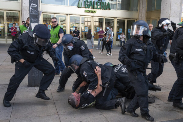 Police officers apprehend a man at a demonstration on Alexanderplatz in Berlin, Germany after several hundred people gathered for an unsanctioned demonstration Saturday May 9, 2020. According to a spokesperson, police officers pointed out to the demonstrators the regulations for containing the coronavirus pandemic. (Christophe Gateau/DPA via AP)