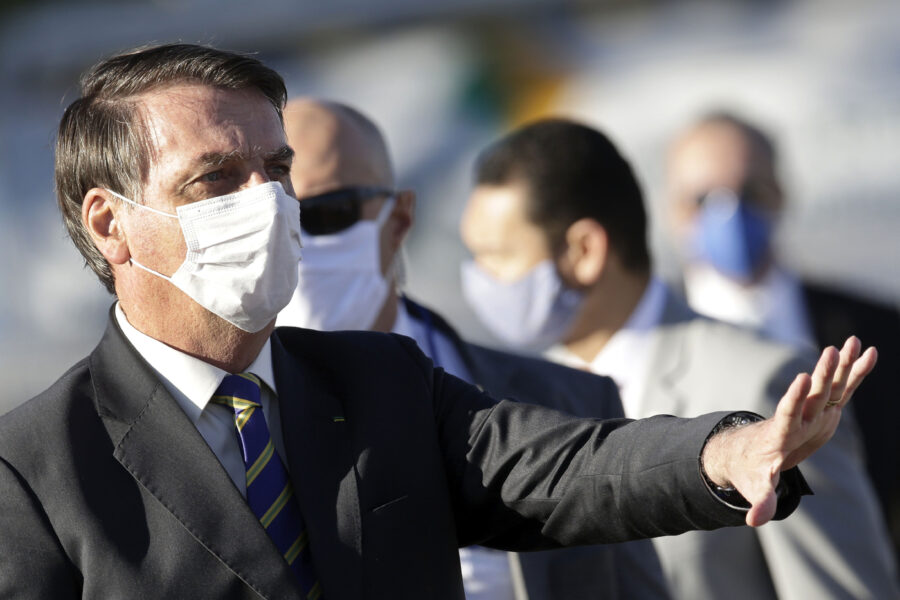 Brazil's President Jair Bolsonaro gestures to supporters before the start of a flag raising ceremony outside Alvorada palace, the presidential residence in Brasilia, Brazil, Tuesday, May 12, 2020. The morning ceremony flew Brazil's flag at half mast to mourn those who have died from the new coronavirus. (AP Photo/Eraldo Peres)