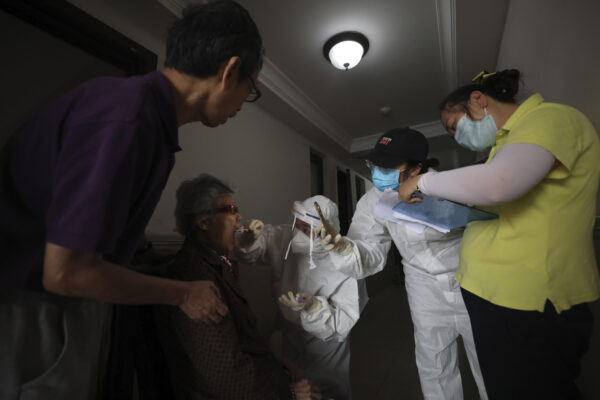 A medical worker takes a swab from a resident for the coronavirus test during home visits in Wuhan the epicenter of China's coronavirus outbreak in central China's Hubei province, Thursday, May 14, 2020. Some residential compounds in Wuhan have begun testing inhabitants for the coronavirus as a program to test everyone in the Chinese city of 11 million people in 10 days got underway (Chinatopix via AP)