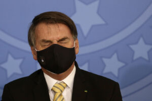 Brazil's President Jair Bolsonaro, wearing a mask amid the COVID-19 pandemic, briefly shuts his eyes during an event promoting a government campaign against domestic violence at Planalto presidential palace in Brasilia, Brazil, Friday, May 15, 2020. (AP Photo/Eraldo Peres)