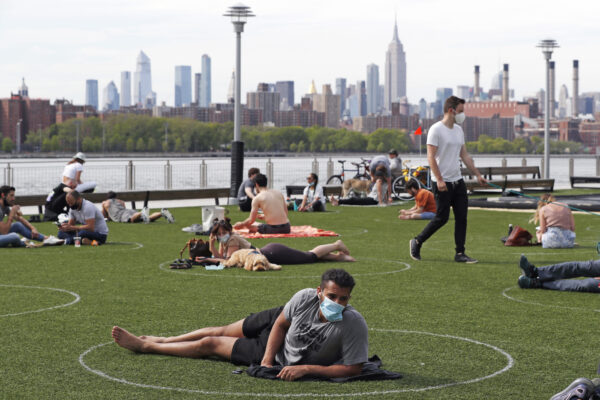 People relax in designated circles marked on the grass at Brooklyn's Domino Park during the current coronavirus outbreak, Monday, May 18, 2020, in New York. The circles were added after the park became severely overcrowded duirng a spate of uneasonably warm weather just over a week ago. (AP Photo/Kathy Willens)