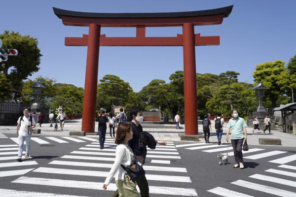 In this May 17, 2020, photo, people walk past the torii, a gateway at the entrance to Tsurugaoka Hachimangu Shinto shrine, in Kamakura, Kanagawa prefecture, near Tokyo. While Kanagawa is still under a coronavirus state of emergency, the pandemic is pitting those willing to follow requests for self-restraint against a sizable minority resisting the calls to stay home. (AP Photo/Shuji Kajiyama)