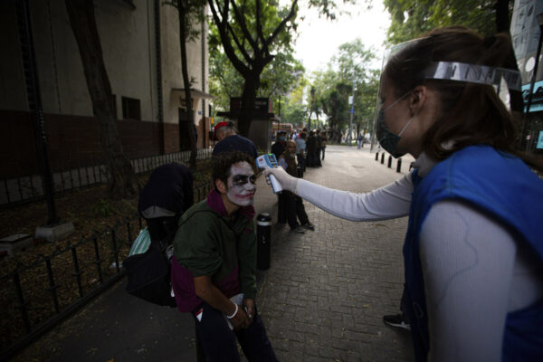 A volunteer takes the temperature of a homeless man with his face painted, screening for COVID-19 symptoms at a line to receive a free meal in Mexico City, Wednesday, May 20, 2020. The volunteers running the soup kitchen say they have had to expand their service from a single day to two days per week as the number of people in need grows. (AP Photo/Fernando Llano)