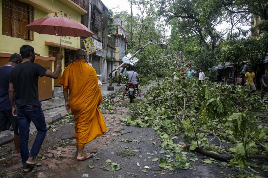 A Buddhist monk walks through a road laid with fallen trees and branches after Cyclone Amphan hit the region in Kolkata, India, Thursday, May 21, 2020. A powerful cyclone ripped through densely populated coastal India and Bangladesh, blowing off roofs and whipping up waves that swallowed embankments and bridges and left entire villages without access to fresh water, electricity and communications. (AP Photo/Bikas Das)