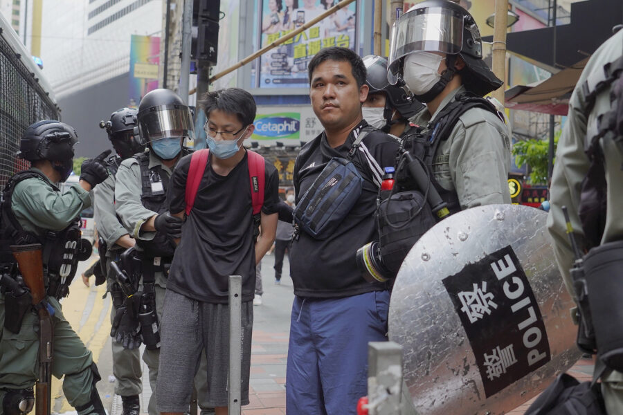 Riot police detain protesters during a demonstration against Beijing's national security legislation in Causeway Bay in Hong Kong, Sunday, May 24, 2020. Hong Kong police fired volleys of tear gas in a popular shopping district as hundreds took to the streets Sunday to march against China's proposed tough national security legislation for the city. (AP Photo/Vincent Yu)
