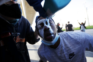 A protester is doused with milk Friday, May 29, 2020, in Minneapolis. Protests continued following the death of George Floyd, who died after being restrained by Minneapolis police officers on Memorial Day. (AP Photo/John Minchillo)