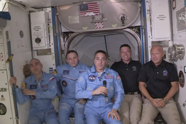 This photo provided by NASA shows Bob Behnken and Doug Hurley, far right, joining the the crew at the International Space Station, after the SpaceX Dragon capsule pulled up to the station and docked Sunday, May 31, 2020.  The Dragon capsule arrived Sunday morning, hours after a historic liftoff from Florida. It's the first time that a privately built and owned spacecraft has delivered a crew to the orbiting lab.(NASA via AP)