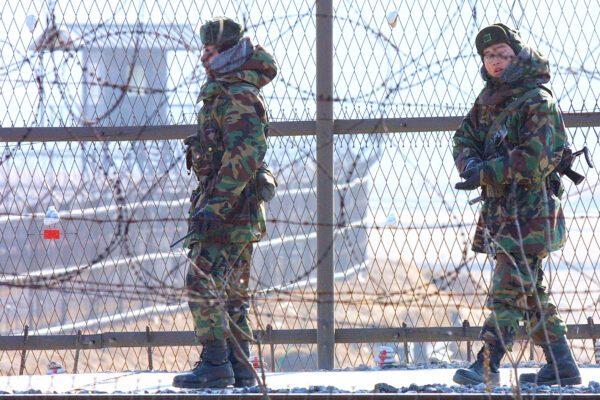©LAPRESSE 01-01-2003, IMJINGAK, COREA DEL SUD ESTERO DUE SOLDATI COREANI CONTROLLANO LA RETE MESSA A PROTEZIONE NEI PRESSI DELLA ZONA DEMILITARIZZATA CHE SEPARA LA COREA DEL SUD DA QUELLA DEL NORD. I SUD COREANI SPERANO IN UNA RISOLUZIONE PACIFICA DELLA CRISI TRA LA COREA DEL NORD E GLI STATI UNITI SCATENATA DALLA RIPRESA DELLA ATTIVITA' NUCLEARE DA PARTE DELLA COREA DEL NORD.