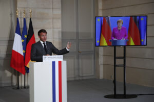 French President Emmanuel Macron speaks while German Chancellor Angela Merkel listens during a joint video press conference at the Elysee Palace Monday, May 18, 2020 in Paris. France and Germany discussed Europe's economic recovery plans to respond to the virus crisis. (AP Photo/Francois Mori, Pool)