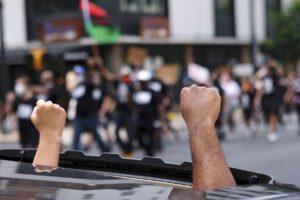 Proteste George Floyd, membro del Ku Klux Klan alla guida dell'auto contro la folla