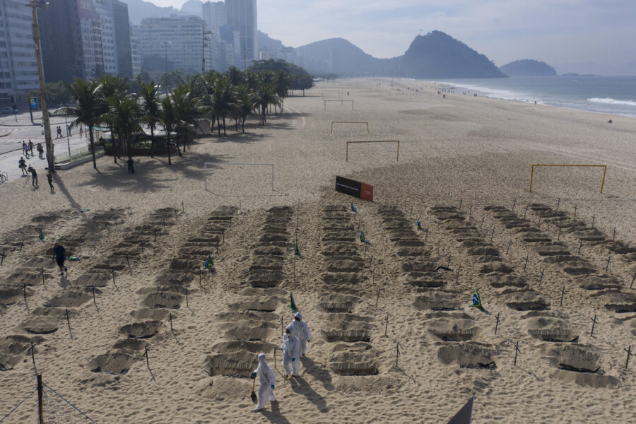 Activists in costume dig symbolic graves on Copacabana beach as a protest, organized by the NGO Rio de Paz, against the government's handling of the COVID-19 pandemic in Rio de Janeiro, Brazil, Thursday, June 11, 2020. A Brazilian Supreme Court justice ordered the government of President Jair Bolsonaro to resume publication of full COVID-19 data, including the cumulative death toll, following allegations the government was trying to hide the severity of the pandemic in Latin America's biggest country. (AP Photo/Leo Correa)