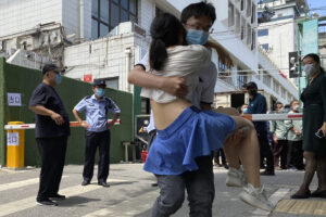 A woman is carried out from a coronavirus testing center set up outside a sports facility in Beijing, Tuesday, June 16, 2020. China reported several dozen more coronavirus infections Tuesday as it increased testing and lockdown measures in parts of the capital to control what appeared to be its largest outbreak in more than two months. (AP Photo/Ng Han Guan)