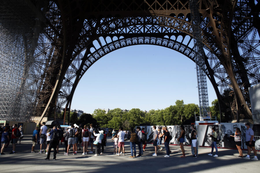 People queue up prior to visit the Eiffel Tower, in Paris, Thursday, June 25, 2020. The Eiffel Tower reopens after the coronavirus pandemic led to the iconic Paris landmark's longest closure since World War II. (AP Photo/Thibault Camus)
