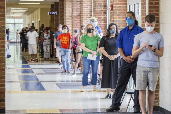 Voters wait in long lines at Peachcrest Elementary School to vote in the state's primary election, Tuesday, June 9, 2020 in Decatur, Ga. Coronavirus restrictions only allow 10 people in the gym at a time so many machines are not being used, creating long wait times.(Jenni Girtman/Atlanta Journal-Constitution via AP)