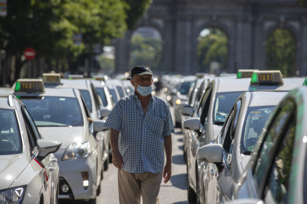 A taxi driver wearing a face mask to prevent the spread of coronavirus walks amid a taxi drivers protest in downtown Madrid, Spain, Tuesday, June 30, 2020. Taxi drivers are demanding  assistance due to lack of clients and private hire. (AP Photo/Manu Fernandez)
