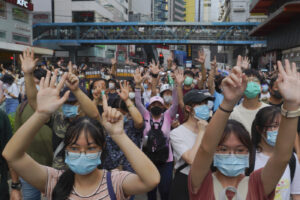 """Protesters against the new national security law march and gesture with five fingers, signifying the """"Five demands – not one less"""" on the anniversary of Hong Kong's handover to China from Britain in Hong Kong, Wednesday, July. 1, 2020. Hong Kong marked the 23rd anniversary of its handover to China in 1997, and just one day after China enacted a national security law that cracks down on protests in the territory. (AP Photo/Vincent Yu)"""