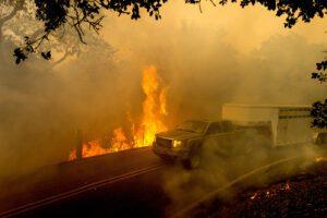 A livestock trailer drives along Canada Road as the Crews Fire burns near Gilroy, Calif., on Sunday, July 5, 2020. (AP Photo/Noah Berger)