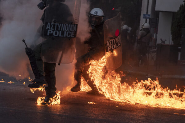 Riot police officers try to avoid patrol bombs thrown by protesters outside the Greek Parliament during a demonstration against new protest law in Athens, on Thursday, July 9, 2020. Violence has broken out in Athens during a mass demonstration against plans to curb public protests. (AP Photo/Petros Giannakouris)