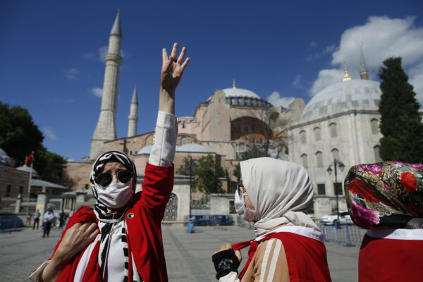People, dropped in Turkish flags, chant slogans, outside the Byzantine-era Hagia Sophia, one of Istanbul's main tourist attractions in the historic Sultanahmet district of Istanbul, following Turkey's Council of State's decision, Friday, July 10, 2020.Turkey's Council of State, threw its weight behind a petition brought by a religious group and annulled a 1934 cabinet decision that changed the 6th century building into a museum. The ruling allows the government to restore the Hagia Sophia's previous status as a mosque.The decision was in line with the Turkish President's Recep Tayyip Erdogan's calls to turn the hugely symbolic world heritage site into a mosque despite widespread international criticism, including from the United States and Orthodox Christian leaders. (AP Photo/Emrah Gurel)