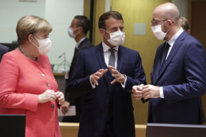 European Council President Charles Michel, right, speaks with French President Emmanuel Macron, center, and German Chancellor Angela Merkel during a round table meeting at an EU summit in Brussels, Friday, July 17, 2020. Leaders from 27 European Union nations meet face-to-face on Friday for the first time since February, despite the dangers of the coronavirus pandemic, to assess an overall budget and recovery package spread over seven years estimated at some 1.75 trillion to 1.85 trillion euros. (Stephanie Lecocq, Pool Photo via AP)